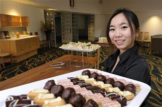 Celeste Catering staff member holding a platter of sweets